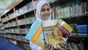 Seorang siswi menunjukan buku pelajaran baru kurikulum 2013 di SMA 68 Jakarta (15/07). Di mulai hari ini Kemendikbud menerapkan kurikulum baru 2013 saat seluruh siswa dan siswi masuk sekolah hari pertama. TEMPO/Dasril Roszandi